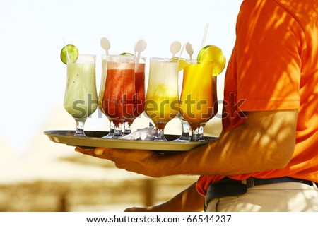 Waiter serving drinks / cocktails on the beach