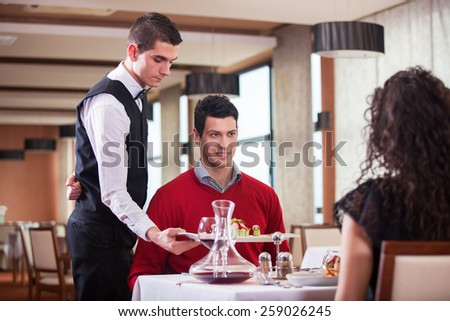 Waiter serving food in a restaurant - stock photo