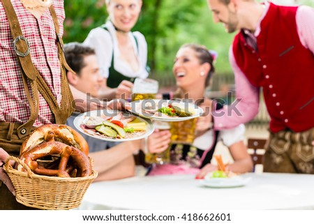 Waiter serving food in Bavarian beer garden, people eating and drinking in background - stock photo