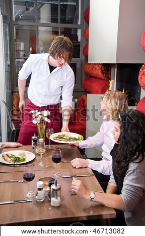 Waiter serving food to restaurant customers - stock photo