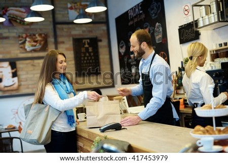 Waiter serving guest in cafeteria. Placing takeaway order on counter. - stock photo