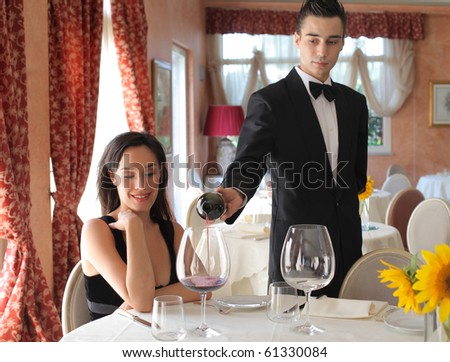 Waiter serving some wine to a beautiful woman in a luxury restaurant - stock photo