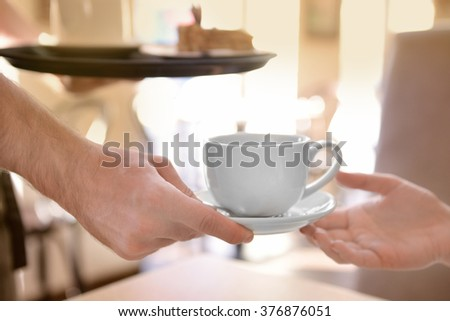 Waiter serving tea to customer in cafe