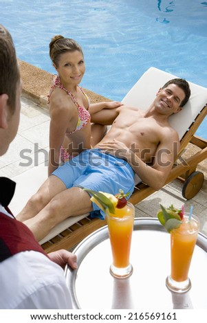 Waiter serving tropical drinks to couple on lounge chair at poolside - stock photo