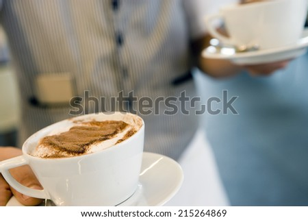 Waiter serving two capuchinos in cafe, close-up, mid-section, focus on foreground - stock photo