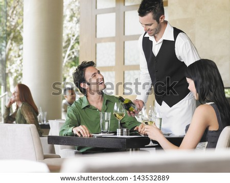 Waiter serving wine to young couple at outdoor restaurant - stock photo