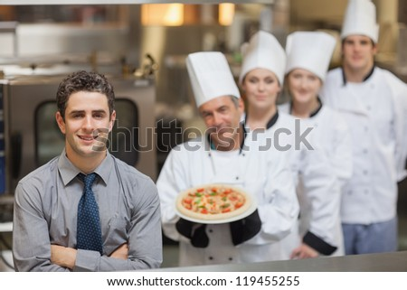 Waiter standing in front of Chef's holding a pizza - stock photo