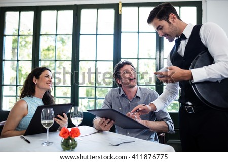 Waiter taking an order for a couple in a restaurant - stock photo