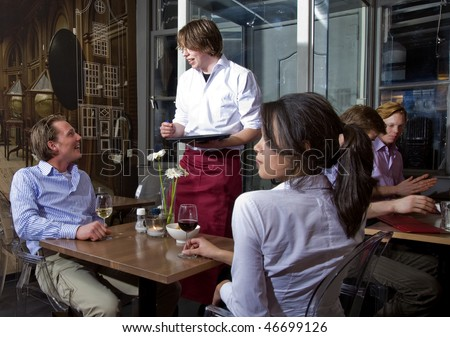waiter taking orders from a customer in a restaurant - stock photo
