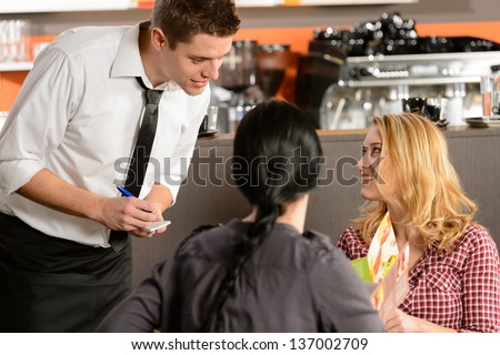 Waiter taking orders from young woman customer in restaurant - stock photo