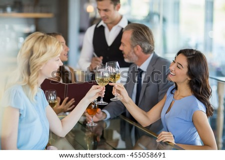 Waiter taking the order while colleagues toasting glasses of wine in restaurant