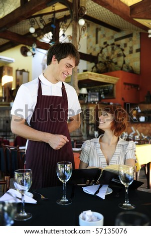 waiter talking to costumer at the restaurant - stock photo