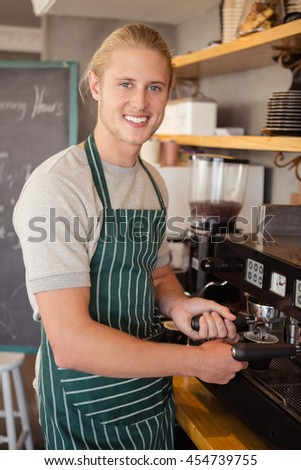 Waiter using coffee machine in cafeteria