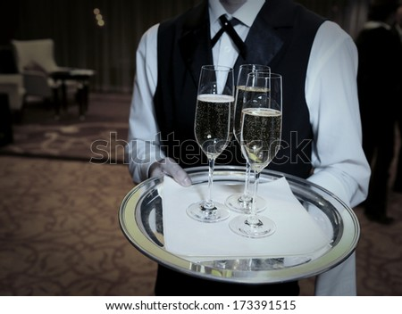 Waiter welcomes guests with champagne - stock photo