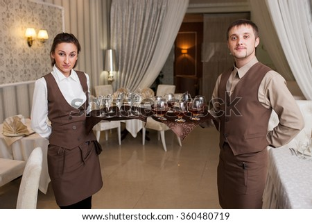 waiter with a tray welcomes visitors