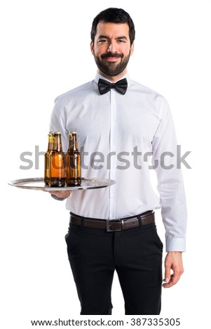 Waiter with beer bottles on the tray - stock photo