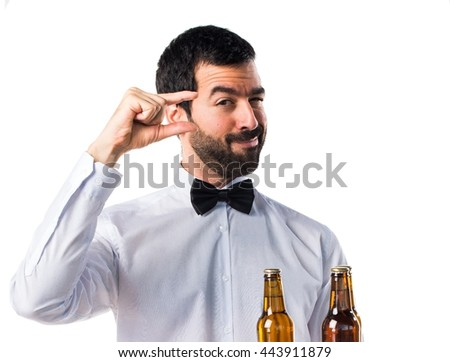 Waiter with beer bottles on the tray doing tiny sign - stock photo