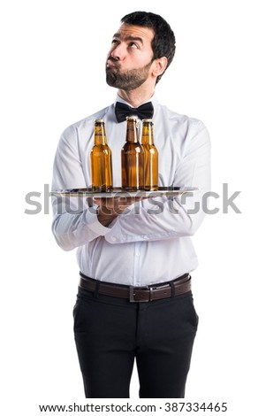 Waiter with beer bottles on the tray having doubts