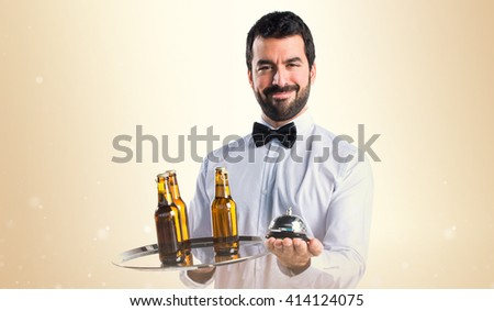 Waiter with beer bottles on the tray holding a bell - stock photo