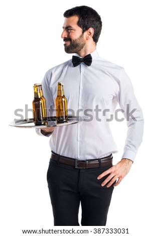 Waiter with beer bottles on the tray looking lateral