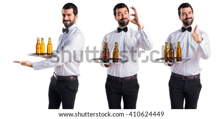 Waiter with beer bottles on the tray presenting something - stock photo