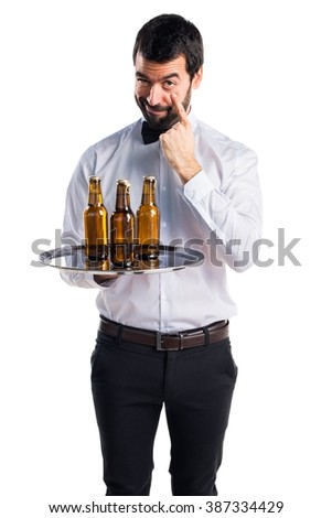 Waiter with beer bottles on the tray showing something