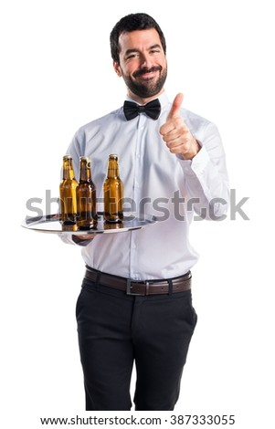 Waiter with beer bottles on the tray with thumb up