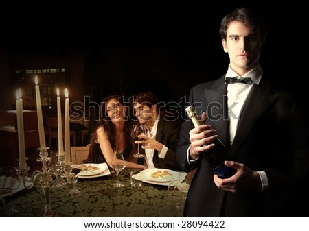 Waiter with bottle of wine and a couple on the background - stock photo
