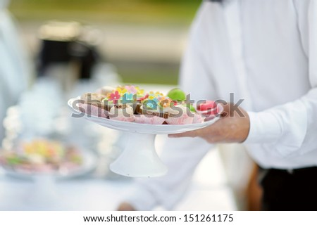Waiter with dish of colorful cupcakes