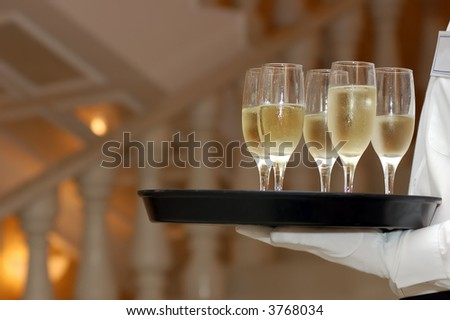 waiter with dish of vine glasses - stock photo