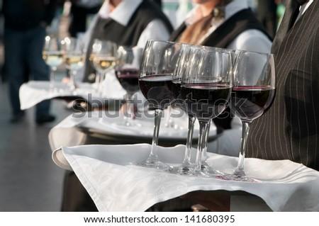 Waiter with dish of wine glasses - stock photo