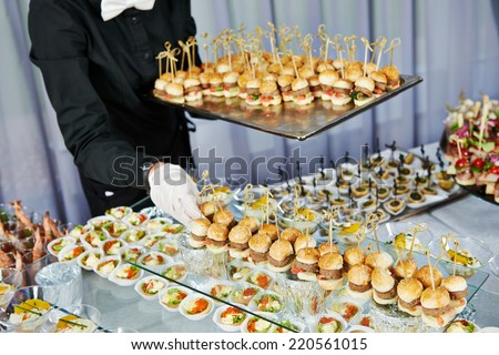 Waiter with meat dish serving catering table with food snacks  - stock photo