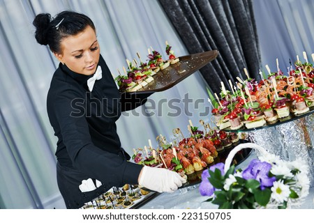 Waiter with meat dish serving catering table with food snacks during party event - stock photo