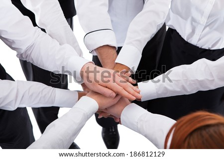 Waiters and waitresses stacking hands. Isolated on white - stock photo