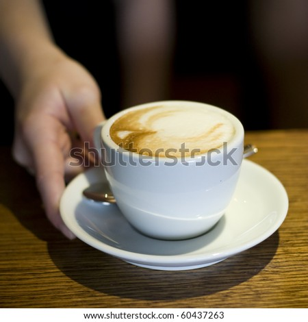 waiters hand gives cappuccino - stock photo