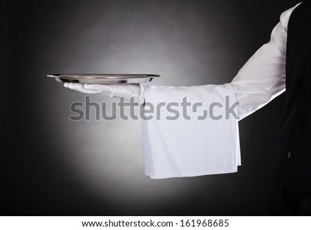 Waiters Hand Holding Tray Over Black Background - stock photo