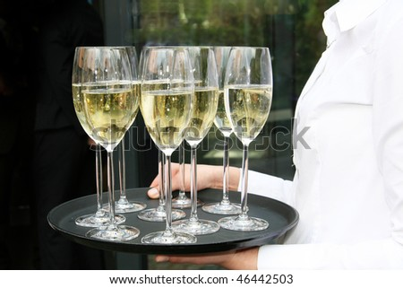 Waiters served champagne glasses on a tray. - stock photo