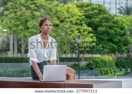 Waiting business solutions over laptop in Dubai. Smiling African businesswoman businessman sitting in the street and working at a laptop in Dubai downtown among green trees while looking ahead - stock photo