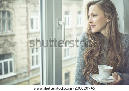waiting by the window woman with tea. concept - stock photo