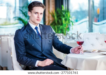 Waiting contract. Confident businessman in formal wear sitting at a table in a restaurant while holding a glass of wine and looking at the camera - stock photo
