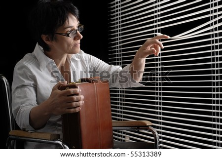 Waiting disabled business woman in wheelchair looking trough closed blinds