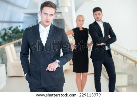 Waiting for business decision. Young and successful businessman is standing and looking confidently into the camera, while two his colleagues are standing on the background communicating - stock photo