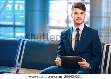 Waiting for his flight. Portrait of handsome smiling businessman in formalwear holding a digital tablet while sitting in the airport in business lounge  - stock photo