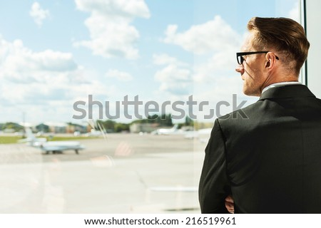 Waiting for his flight. Rear view of thoughtful businessman in formalwear looking through a window in airport  - stock photo