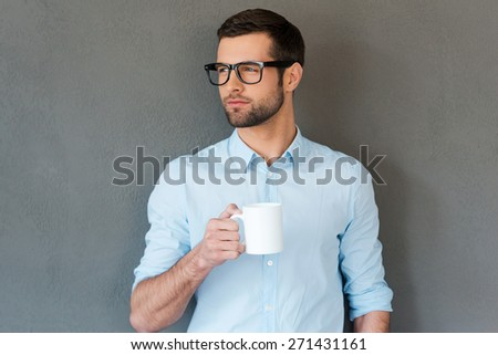 Waiting for inspiration. Handsome young man in shirt in eyewear holding cup of coffee and looking way while standing against grey background  - stock photo