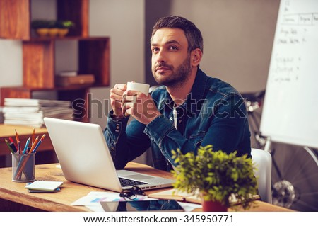 Waiting for inspiration. Thoughtful young man holding coffee cup and looking away while sitting at his working place in office - stock photo