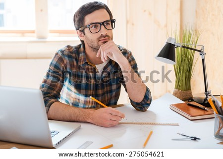 Waiting for inspiration. Thoughtful young man holding hand on chin and looking away while sitting at his working place - stock photo