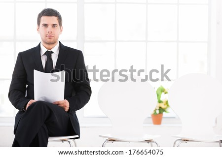 Waiting for job interview. Confident young man in formalwear sitting at the chair and holding head in hand while other chairs standing in a row - stock photo