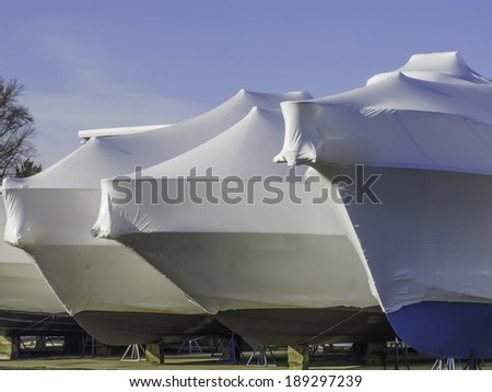 Waiting for nice weather is part of a lifestyle: Bows of shrink-wrapped yachts in boatyard on a sunny morning, spring in southwestern Michigan - stock photo