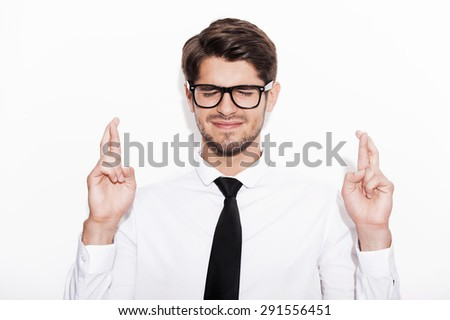 Waiting for special moment. Young man keeping fingers crossed and eyes closed while standing against white background - stock photo